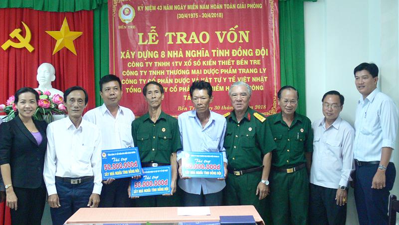 Các đại biểu chụp ảnh lưu niệm với các hộ nhận vốn xây nhà.