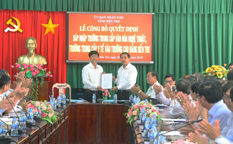 Chủ tịch UBND tỉnh Cao Văn Trọng trao Quyết định sáp nhập cho Quyền hiệu Trưởng nhà trường Võ Thành Phước. Ảnh: Ngân Hà