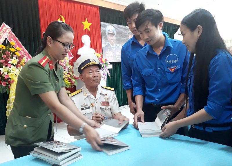 Anh hùng Lực lượng vũ trang nhân dân Nguyễn Văn Đức ký tặng sách cho đoàn viên thanh niên.