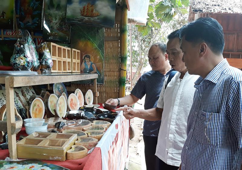 Du khách chọn mua các sản phẩm lưu niệm thủ công mỹ nghệ tại khu du lịch Cồn Phụng.