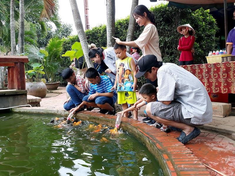 Du khách trải nghiệm cho cá bú bình tại Khu du lịch Cồn Phụng.