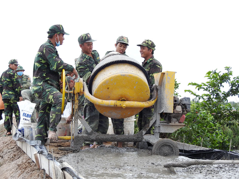 Các chiến sĩ đội Hành quân xanh Bộ Chỉ huy Bộ đội Biên phòng tỉnh bê-tông tuyến đường ấp Giao Tân, xã Giao Thạnh, huyện Thạnh Phú.