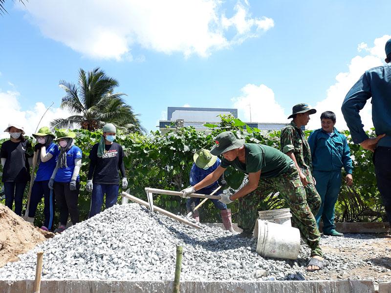 Đội hình Hành quân xanh Bộ Chỉ huy Quân sự tỉnh thi công đường giao thông nông thôn ở ấp Phú Thới, xã Tân Thiềng, huyện Chợ Lách.