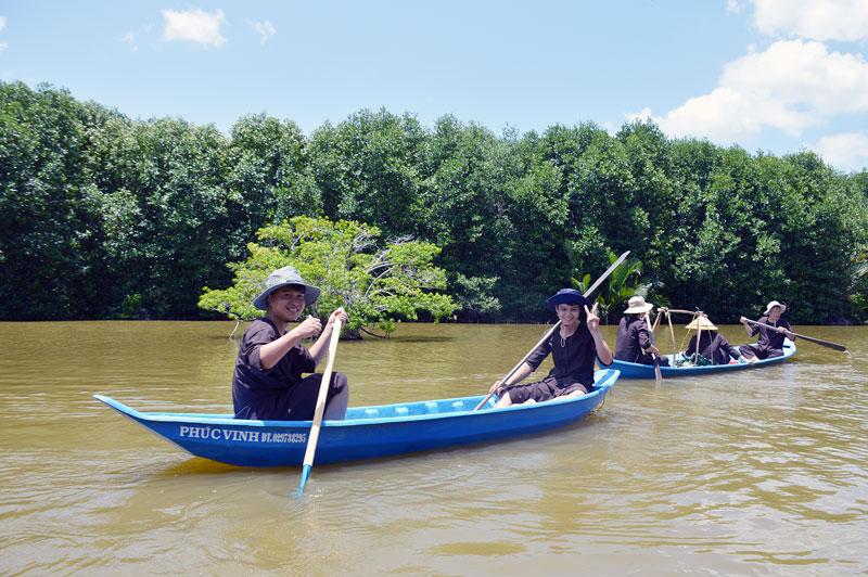 Chèo xuồng bắt cá trong khu du lịch sinh thái rừng.