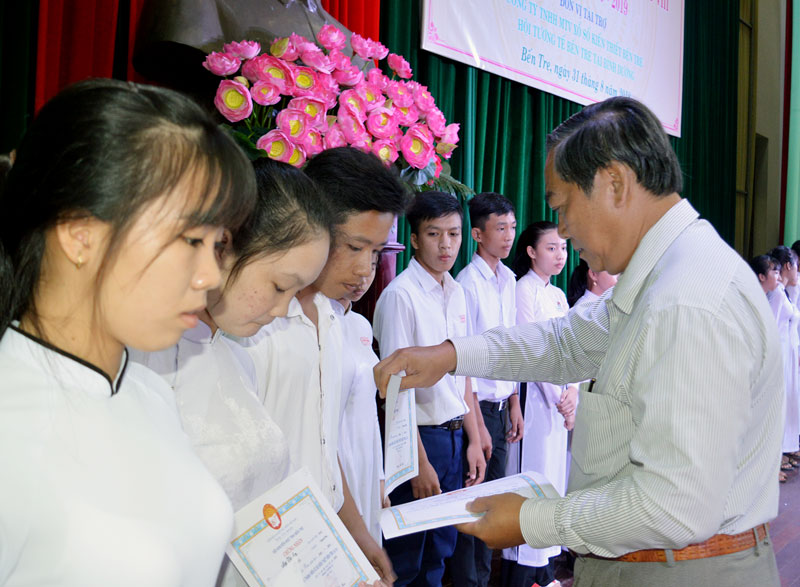 Phó Chủ tịch UBND tỉnh Nguyễn Hữu Phước trao học bổng cho các em học sinh. Ảnh: A. Nguyệt