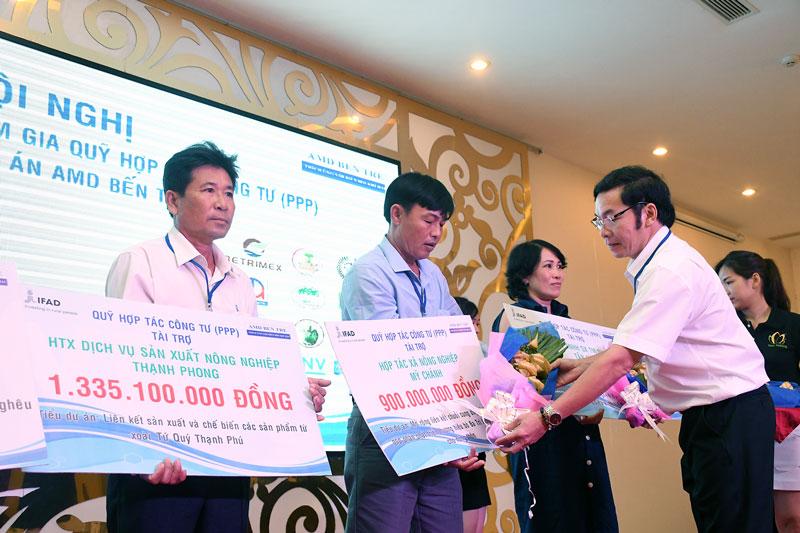 Giám đốc Dự án AMD Bến Tre Lê Khắc Hân trao vốn hỗ trợ cho doanh nghiệp. Ảnh: Thu Huyền