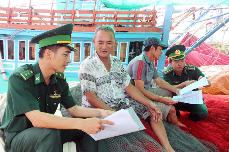 Cán bộ, chiến sĩ Đồn Biên phòng Hàm Luông tuyên truyền pháp luật về chủ quyền biển, đảo cho ngư dân. Ảnh: Đức Chính