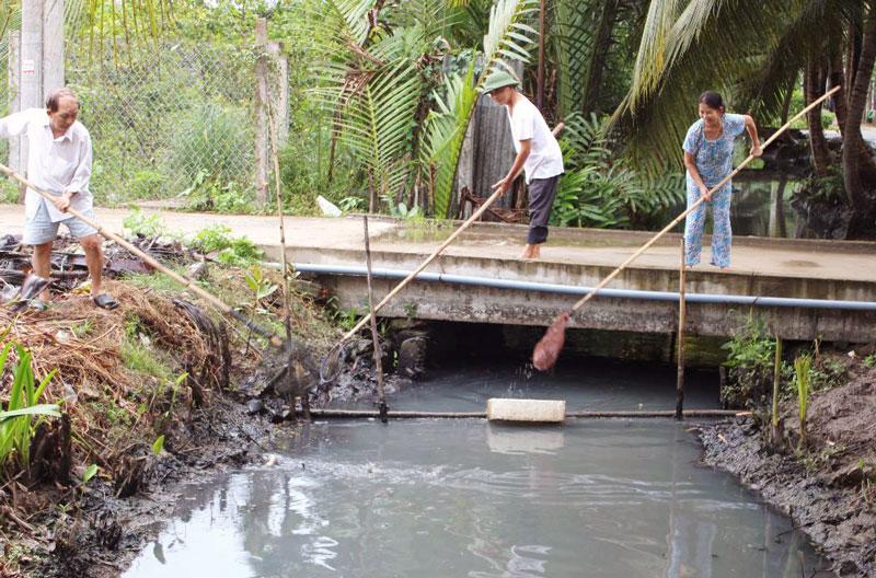Người dân Tổ 2 vớt rác làm sạch lòng kênh Chín Tế.