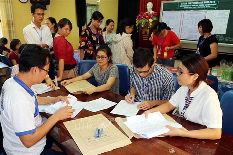 Cán bộ làm công tác thi tại điểm thi Trường THPT Lê Quý Đôn, huyện Trực Ninh (Nam Định) thực hiện niêm phong bài thi theo quy định. Ảnh: Văn Đạt/TTXVN