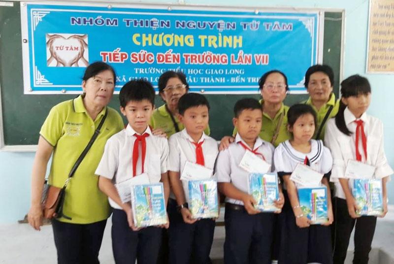 Tặng vở cho các em học sinh Trường Tiểu học Giao Long, huyện Châu Thành.