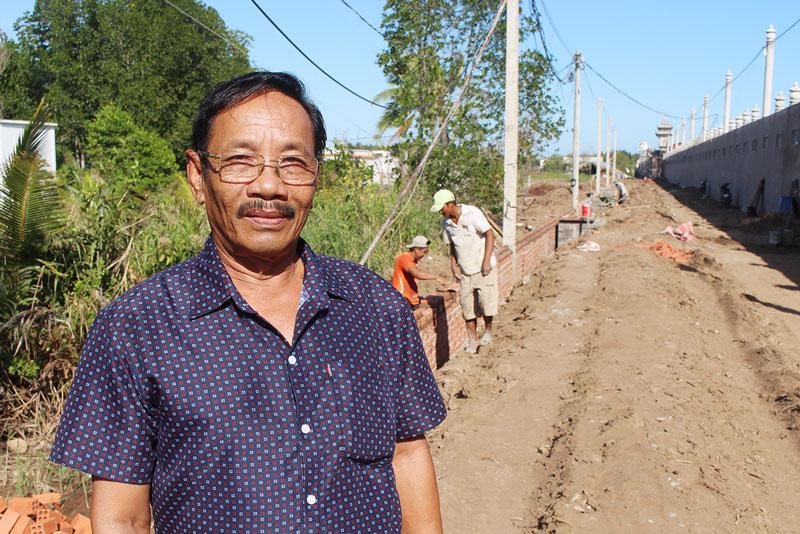Ông Võ Tấn Quang bên con đường bê-tông Tổ 7 đang thi công.