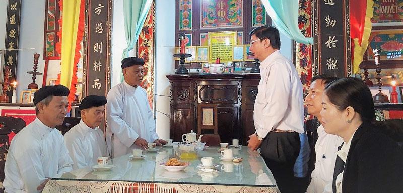 Bí thư Huyện ủy Lê Văn Khê (người đứng bên phải) ghi nhận những đóng góp của các tổ chức tôn giáo. Ảnh: Kim Nương