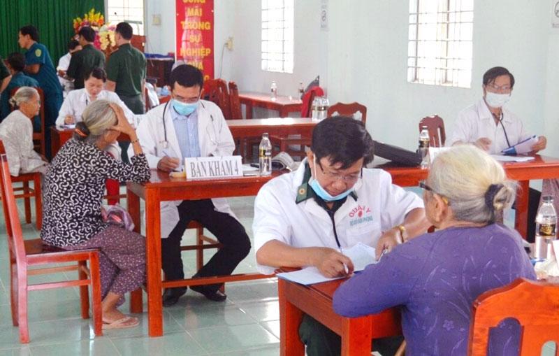 Thiếu tá, bác sĩ Trần Quang Lâm (ngồi bàn đầu) đang khám bệnh cho nhân dân.