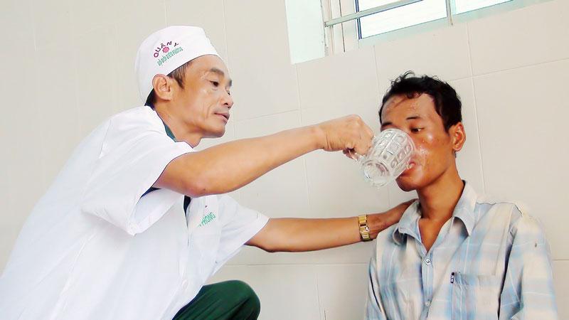 Thiếu tá, y sĩ Trần Ngọc Bình đang chăm sóc thuyền viên vừa được cứu nạn trên biển.
