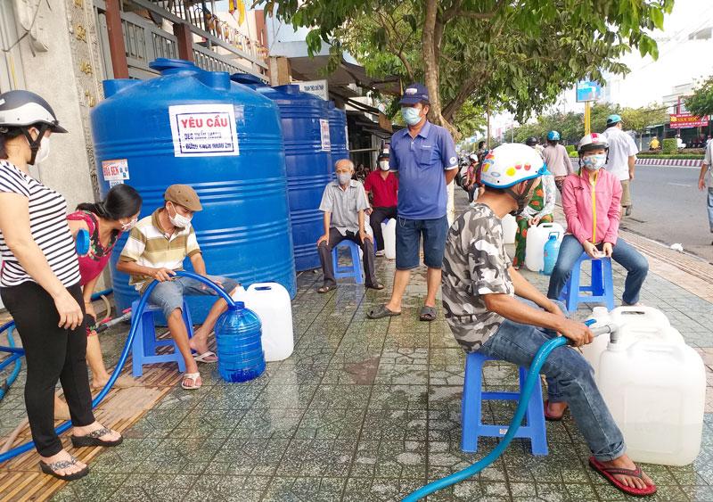 Người dân xếp hàng trật tự chờ lấy nước ngọt miễn phí tại một điểm cấp nước ở phường Phú Khương, TP. Bến Tre.