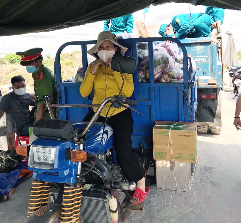 Chị Nguyễn Thị Ngọc Bích chở hàng hóa tới chốt cách ly trạm cầu Thừa Lợi hỗ trợ cho người dân. Ảnh: H. Đức