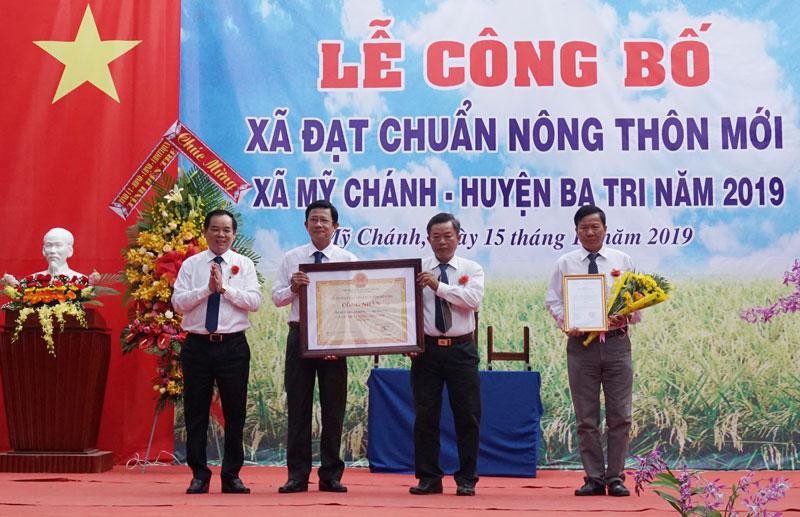 Phó bí thư Thường trực Tỉnh ủy Trần Ngọc Tam trao bằng công nhận xã đạt chuẩn nông thôn mới cho lãnh đạo xã Mỹ Chánh.