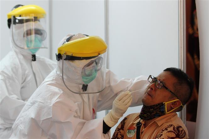 Nhân viên y tế lấy mẫu dịch xét nghiệm COVID-19 cho người dân tại Surakarta, Indonesia ngày 18-7-2020. Ảnh: THX/TTXVN