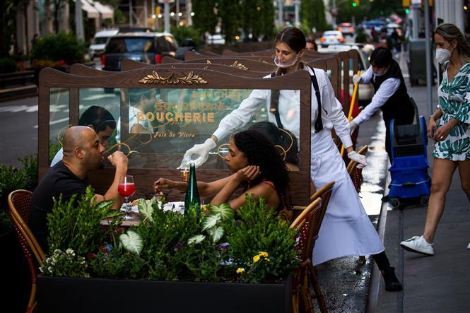 Người dân dùng bữa tại một nhà hàng ngoài trời ở New York, Mỹ, ngày 25-6-2020. Ảnh: THX/TTXVN