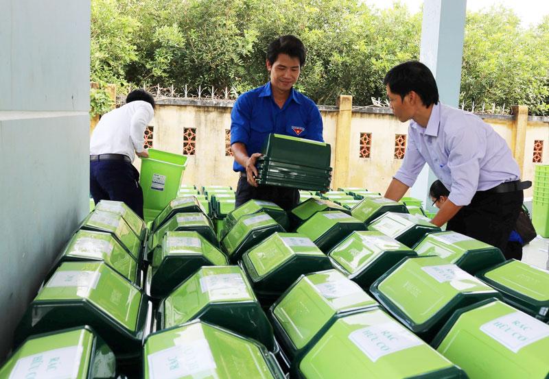 Lực lượng đoàn thanh niên hỗ trợ thùng phân loại rác tại xã Phú Thuận (Bình Đại).