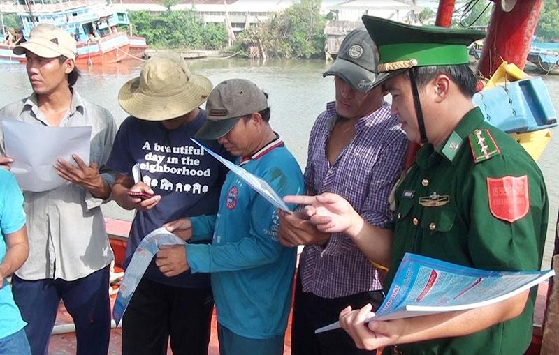 Cán bộ Trạm Kiểm soát biên phòng Bình Thắng (Bình Đại) phát tờ rơi tuyên truyền pháp luật cho các ngư dân. Ảnh: B.Cương