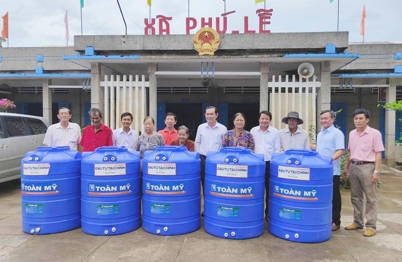 Lãnh đạo xã Phú Lễ và đại diện nhà tài trợ trao bồn chứa nước ngọt hỗ trợ cho người dân.