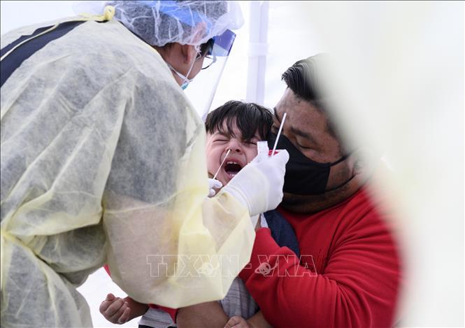 Nhân viên y tế lấy mẫu xét nghiệm COVID-19 tại Compton, California Mỹ. Ảnh: AFP/TTXVN