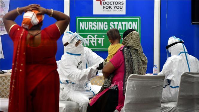 Nhân viên y tế kiểm tra sức khỏe của bệnh nhân COVID-19 tại New Delhi, Ấn Độ ngày 24-7-2020. Ảnh: THX/TTXVN