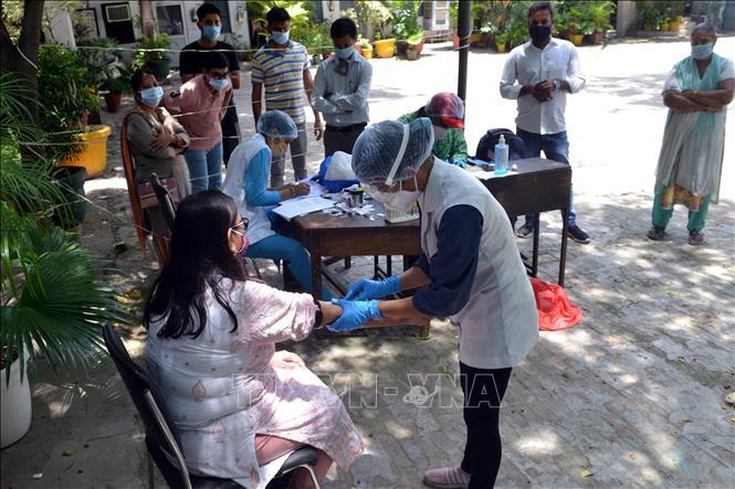 Nhân viên y tế lấy máu xét nghiệm COVID-19 cho người dân tại New Delhi, Ấn Độ ngày 6-8-2020. Ảnh: THX/TTXVN