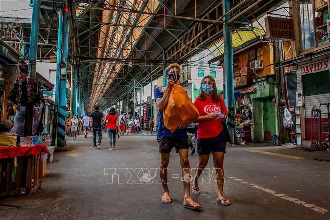 Người dân đeo khẩu trang và tấm chắn khi mua sắm tại một khu chợ ở Manila, Philippines ngày 16-8-2020. Ảnh: THX/TTXVN