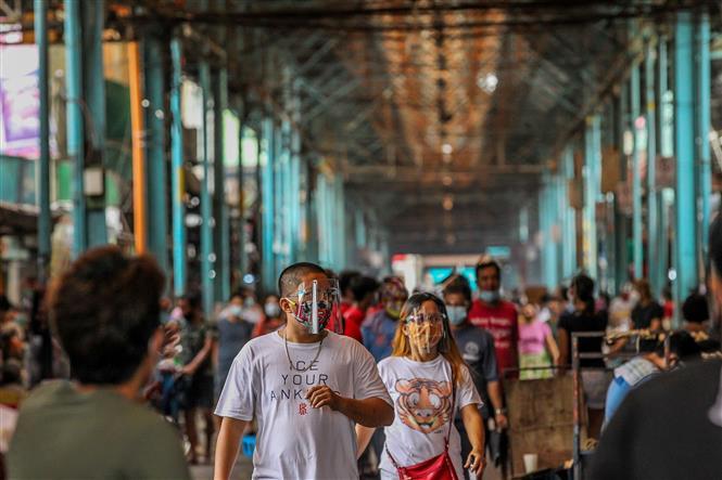 Người dân đeo khẩu trang và tấm chắn nhằm ngăn chặn sự lây lan của dịch COVID-19 khi mua sắm tại một khu chợ ở Manila, Philippines ngày 16-8-2020. Ảnh: THX/TTXVN
