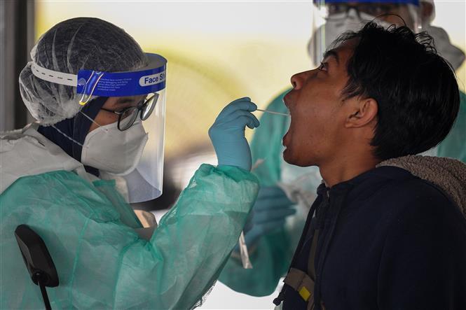 Nhân viên y tế lấy mẫu xét nghiệm COVID-19 cho người dân tại Kuala Lumpur, Malaysia. Ảnh: AFP/TTXVN