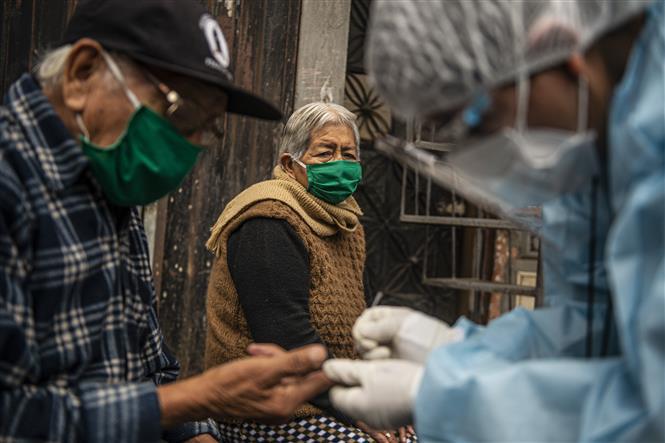 Nhân viên y tế lấy mẫu xét nghiệm COVID-19 cho người dân tại quận Santa Anita, Lima, Peru ngày 20-8-2020. Ảnh: AFP/TTXVN