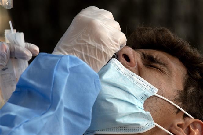 Nhân viên y tế lấy mẫu dịch xét nghiệm COVID-19 cho người dân tại Rome, Italy, ngày 18-8-2020. Ảnh: AFP/TTXVN