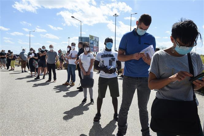 Người dân thực hiện giãn cách xã hội khi xếp hàng lấy mẫu xét nghiệm COVID-19 tại Parc Manceau, Le Mans, Pháp ngày 21-8-2020. Ảnh: AFP/TTXVN