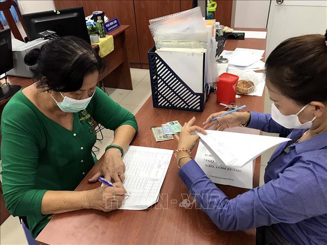 Cán bộ Phường 1, Quận 3 (TP. Hồ Chí Minh) chi trả hỗ trợ người lao động bị ảnh hưởng bởi dịch COVID-19. Ảnh: Thanh Vũ/TTXVN