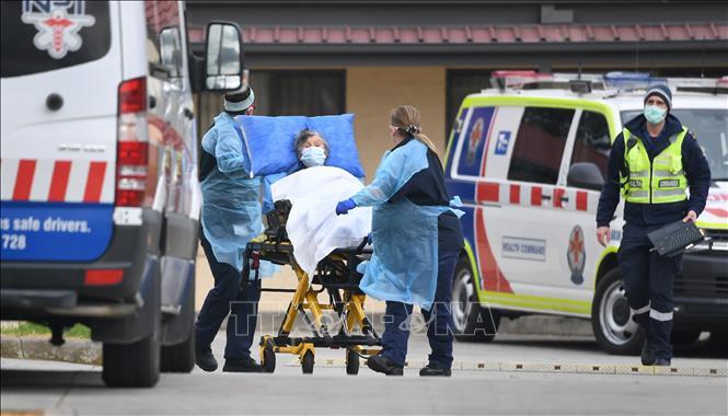 Nhân viên y tế chuyển bệnh nhân mắc COVID-19 lên xe cứu thương tại ngoại ô thành phố Melbourne, bang Victoria, Australia ngày 27-7-2020. Ảnh: AFP/TTXVN