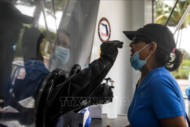Nhân viên y tế lấy mẫu xét nghiệm COVID-19 cho người dân tại Miami Beach, bang Florida, Mỹ ngày 24-7-2020. Ảnh: AFP/TTXVN