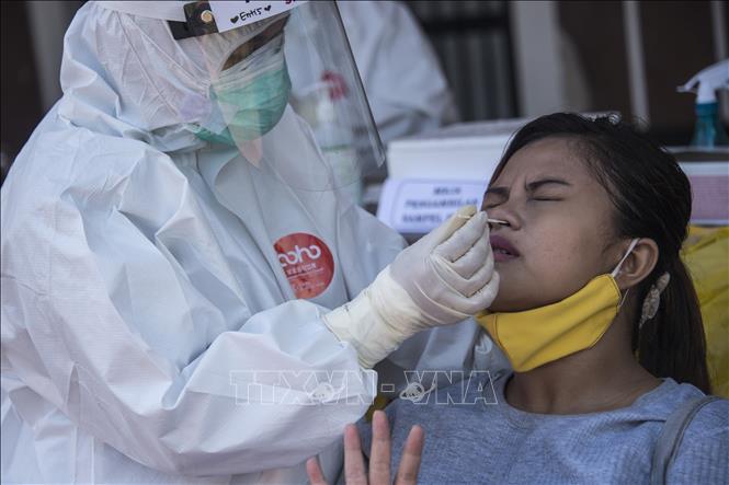 Nhân viên y tế lấy mẫu xét nghiệm COVID-19 cho người dân tại Surabaya, Indonesia ngày 21-7-2020. Ảnh: AFP/TTXVN