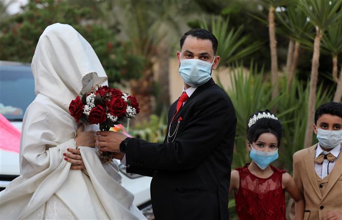 Cô dâu chú rể đeo khẩu trang phòng lây nhiễm COVID-19 trong đám cưới tại Khan Younis, Dải Gaza, ngày 31-8-2020. Ảnh: THX/TTXVN