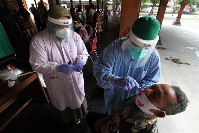 Nhân viên y tế lấy mẫu xét nghiệm COVID-19 tại Surakarta, Indonesia. Ảnh: THX/TTXVN