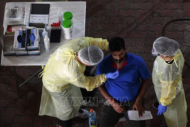 Nhân viên y tế lấy mẫu dịch xét nghiệm COVID-19 cho người lao động tại Singapore ngày 10-6-2020. Ảnh: AFP/TTXVN