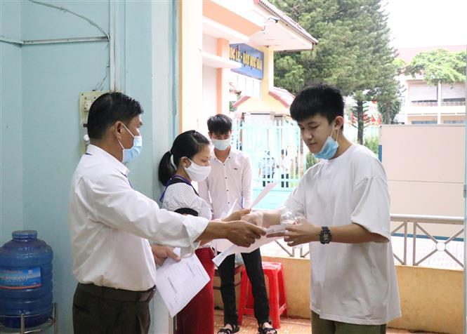 Cán bộ coi thi gọi thí sinh vào phòng thi tại Điểm thi Trường THPT Chu Văn An, thành phố Buôn Ma Thuột, Đắk Lắk. Ảnh: Tuấn Anh/TTXVN