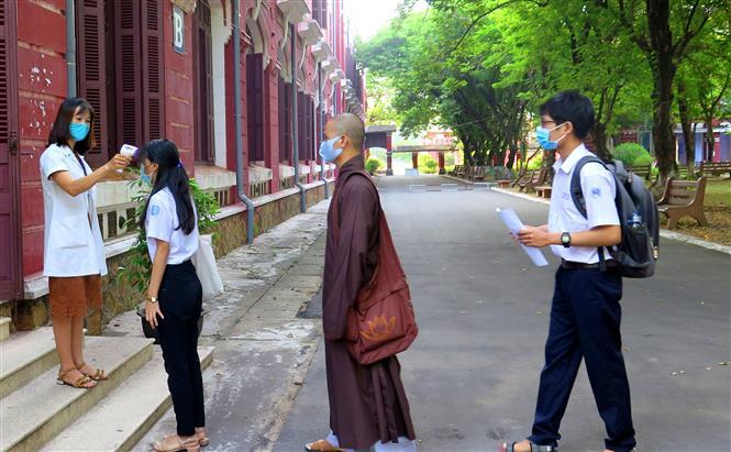 Lực lượng y tế đo thân nhiệt cho các thí sinh trước khi vào phòng thi của tỉnh Thừa Thiên - Huế. Ảnh: Tường Vi /TTXVN