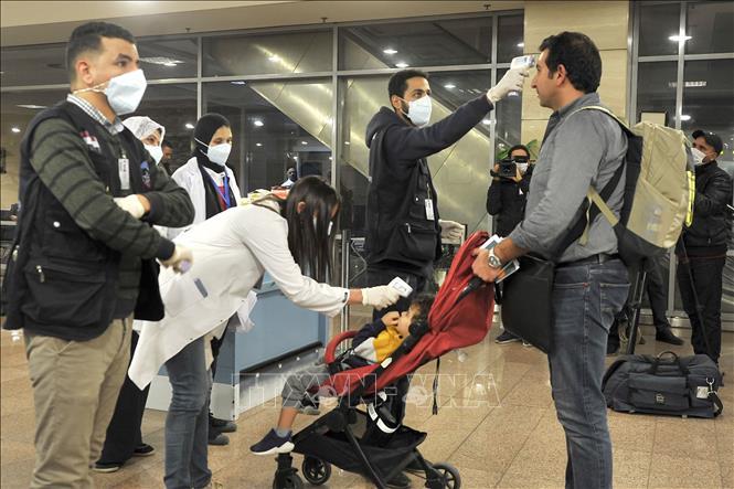 Kiểm tra thân nhiệt nhằm ngăn chặn sự lây lan của COVID-19 tại sân bay quốc tế Cairo, Ai Cập. Ảnh: AFP/TTXVN