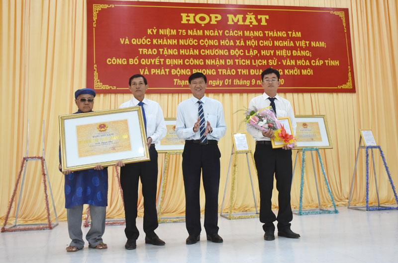 Phó chủ tịch UBND huyện Thạnh Phú Nguyễn Ngọc Tân trao quyết định công nhận di tích và bằng khen của UBND tỉnh cho các đơn vị. Ảnh: Cẩm Trúc
