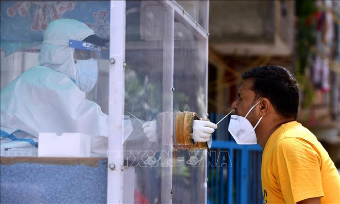 Nhân viên y tế lấy mẫu dịch xét nghiệm COVID-19 cho người dân tại New Delhi, Ấn Độ ngày 22-8-2020. Ảnh: THX/TTXVN