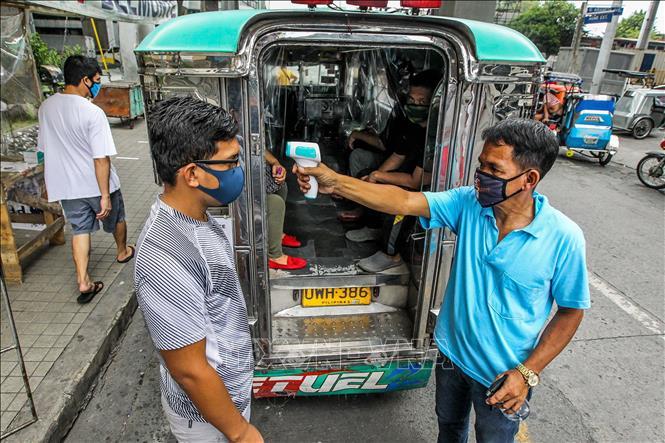 Kiểm tra thân nhiệt nhằm ngăn chặn sự lây lan của dịch COVID-19 tại Manila, Philippines. Ảnh: THX/TTXVN