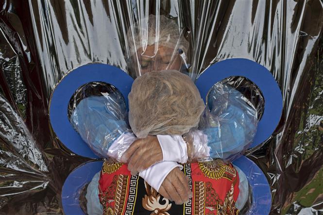 Một bệnh nhân gặp gỡ người thân qua tấm nhựa chắn nhằm ngăn sự lây lan của dịch COVID-19 ở San Salvador, En Salvador, ngày 11-9-2020. Ảnh: AFP/TTXVN