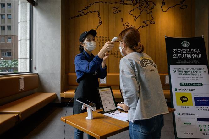 Kiểm tra thân nhiệt phòng lây nhiễm COVID-19 tại một quán cà phê ở Seoul, Hàn Quốc. Ảnh: AFP/TTXVN